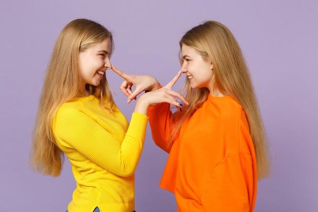 Zijaanzicht van twee grappige blonde tweelingzusters meisjes in kleurrijke kleding die vingers op de neus zetten met plezier geïsoleerd op pastel violet blauwe muur. mensen familie levensstijl concept.