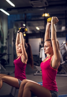 Zijaanzicht van twee jonge gemotiveerde aantrekkelijke gezonde sportieve actieve slanke dames die oefeningen doen en opwarmen met gewichten terwijl ze op de steppers in de sportschool zitten.