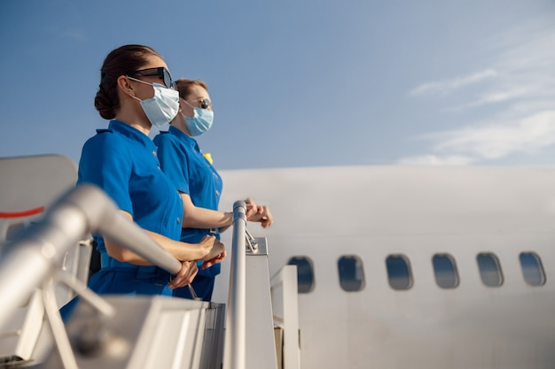 Zijaanzicht van twee jonge stewardessen in blauw uniform, zonnebril en beschermende gezichtsmaskers die wegkijken, staande op de airstair tijdens het instappen. vliegtuigbemanning, bezetting, covid19-concept