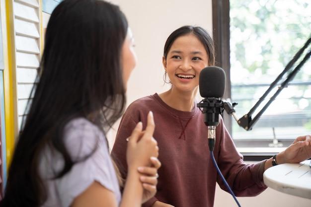Zijaanzicht van twee meisjes die lachen terwijl ze een dialoog voeren in een podcastshow met een microfoon