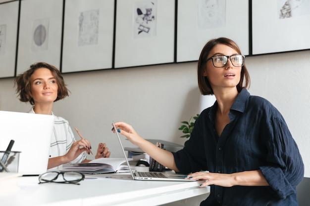 Zijaanzicht van twee mooie vrouwen zitten bij de tafel