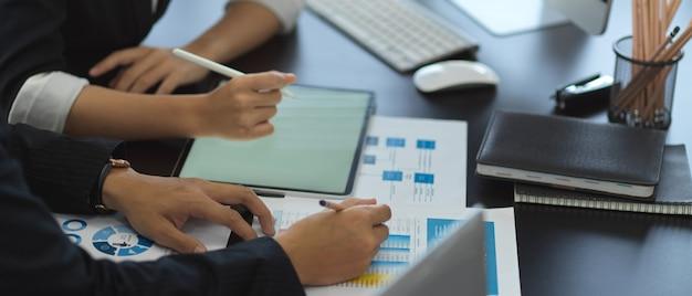 Zijaanzicht van twee ondernemers raadplegen over hun werk met zakelijke grafiek en tablet