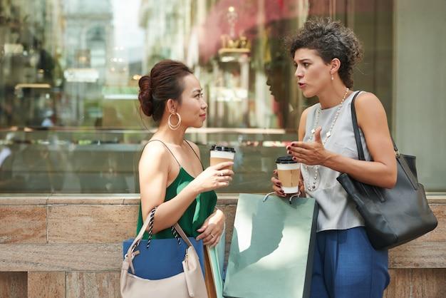 Zijaanzicht van twee roddelmeisjes die bij de koffiewinkel in openlucht spreken