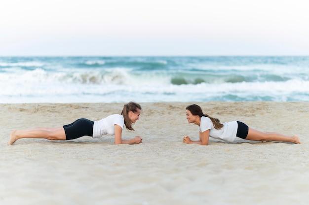 Zijaanzicht van twee vrouwelijke vrienden die op het strand uitoefenen