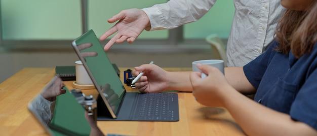 Zijaanzicht van twee vrouwelijke werknemers die over hun project met digitale tablet raadplegen