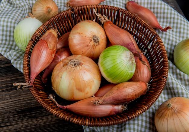 Zijaanzicht van uien als sjalot zoete en witte in mand op geruite doek en houten achtergrond
