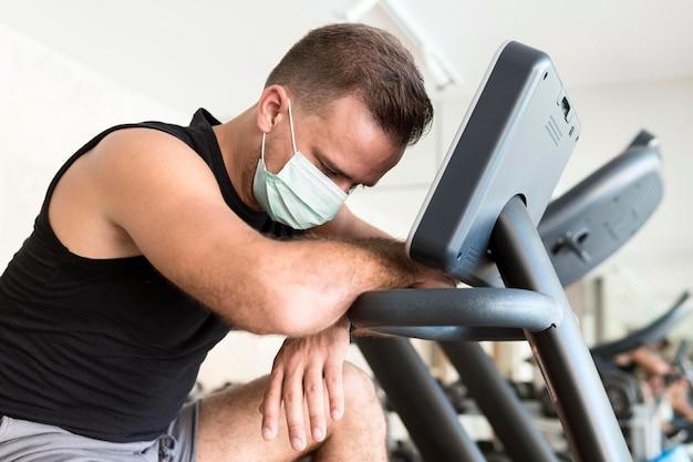 Zijaanzicht van uitgeputte man met medisch masker in de sportschool