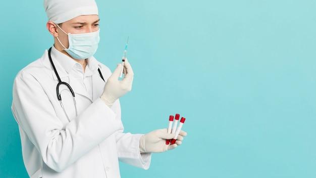 Zijaanzicht van vacutainers van de artsenholding en het bekijken spuit