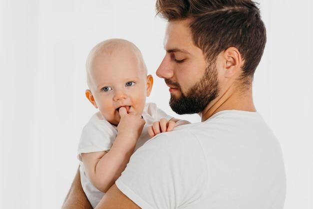 Zijaanzicht van vader die zijn baby houdt