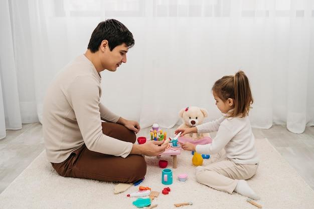 Zijaanzicht van vader en dochter samen thuis