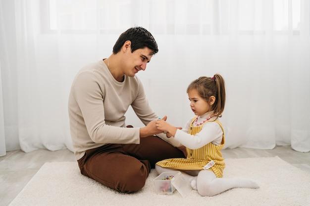 Zijaanzicht van vader tijd doorbrengen met zijn dochter thuis