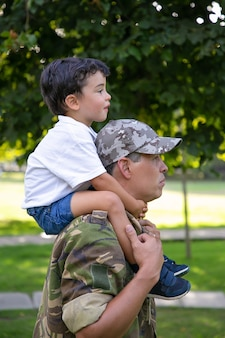 Zijaanzicht van vader zoon op nek houden en wandelen in stadspark. kaukasische zoon zittend op de nek van vader in legeruniform, hem knuffelen en kijken ernaar uit. vaderschap en terugkeer naar huis concept