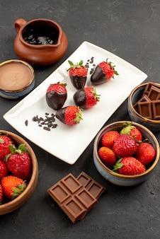 Zijaanzicht van ver chocoladeroom chocoladeroom en aardbeien in kom met chocolade bedekte aardbeien op plaat in het midden van de zwarte tafel