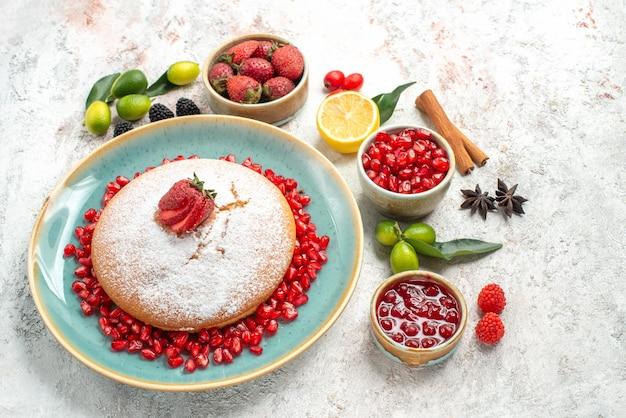 Zijaanzicht van ver de taart een smakelijke taart met aardbeien citroen kaneelstokjes steranijs