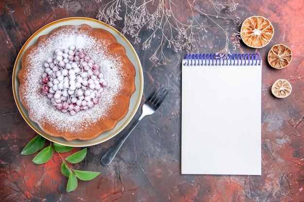 Zijaanzicht van ver een cake een smakelijke cake met bessenbladeren notitieboekje citroenvork
