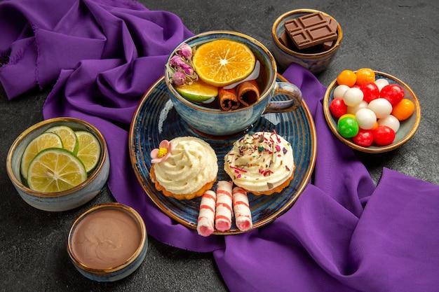 Zijaanzicht van ver een kopje thee blauwe kopje thee met citroen kaneelstokjes kommen chocoladesuikergoed plakjes citrusvruchten en chocoladeroom
