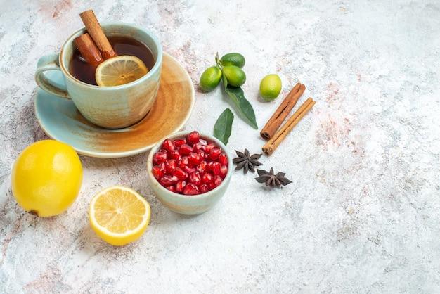 Zijaanzicht van ver een kopje thee citroen zaden van granaatappel steranijs en kaneelstokjes naast het kopje thee met citroen en kaneel op tafel