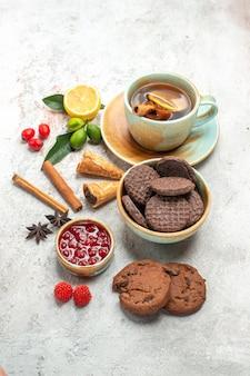 Zijaanzicht van ver een kopje thee een kopje thee chocolade koekjes bessen kaneelstokjes limoenen jam