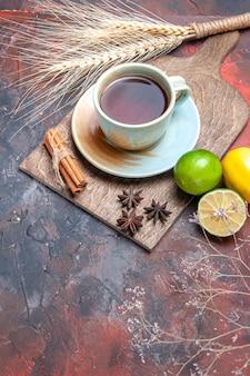 Zijaanzicht van ver een kopje thee een kopje thee kaneelstokjes steranijs citrusvruchten op het bord