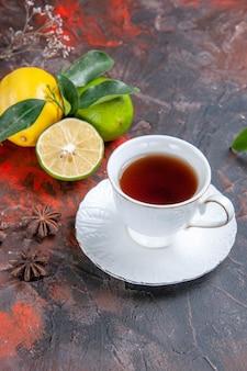 Zijaanzicht van ver een kopje thee een kopje zwarte thee citroenen met bladeren steranijs