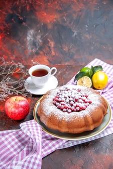 Zijaanzicht van ver een taart een taart met rode aalbessen een kopje thee citrusvruchten op het tafelkleed