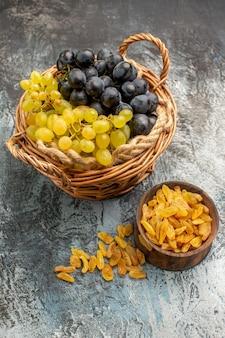 Zijaanzicht van ver fruit de mand met druiven bruine kom gedroogde vruchten