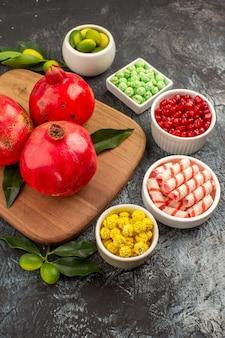 Zijaanzicht van ver granaatappels kom met snoepjes limoenen granaatappels met blaadjes op de snijplank