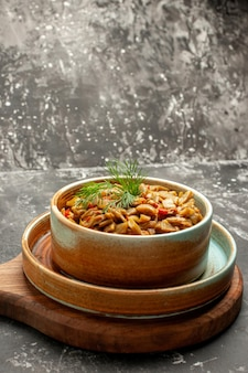 Zijaanzicht van ver smakelijk gerecht de smakelijke sperziebonen en tomaten op de snijplank op de zwarte tafel