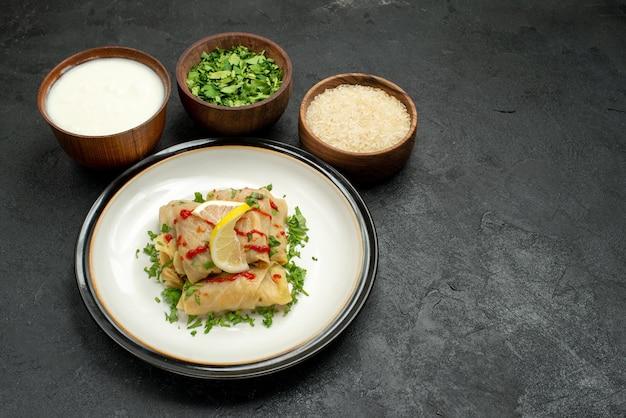 Zijaanzicht van ver smakelijk gerecht smakelijke gevulde kool met kruiden citroen en saus op witte plaat en borden met zure room kruiden en rijst in het midden van zwarte tafel