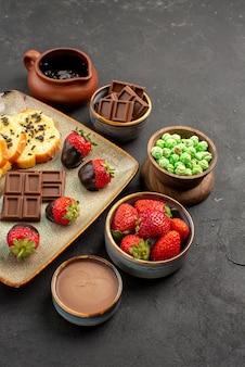 Zijaanzicht van veraf aardbeientaart chocolade kommen van chocolade aardbeien groene snoepjes en chocolade crème smakelijke taart en aardbeien aan de linkerkant van de tafel