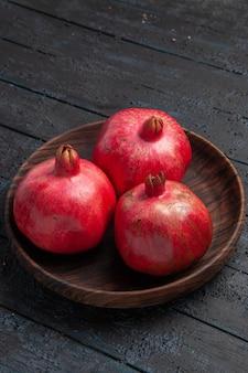 Zijaanzicht van veraf drie granaatappels houten kom granaatappels op grijze tafel