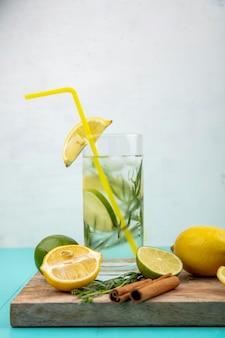 Zijaanzicht van verfrissend zomer detox water met gele citroen op wit