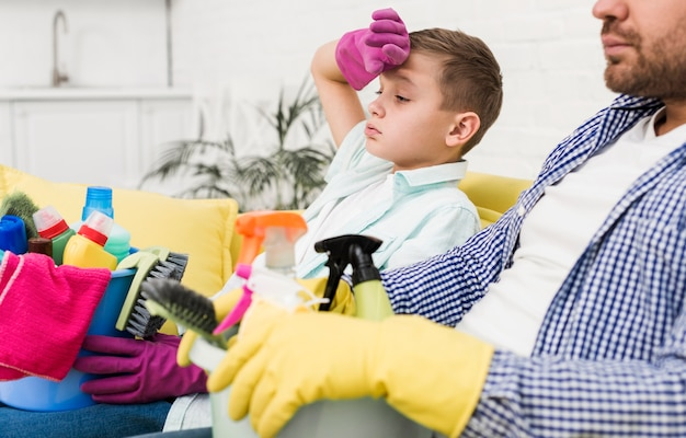 Zijaanzicht van vermoeide vader en zoon na het schoonmaken van het huis