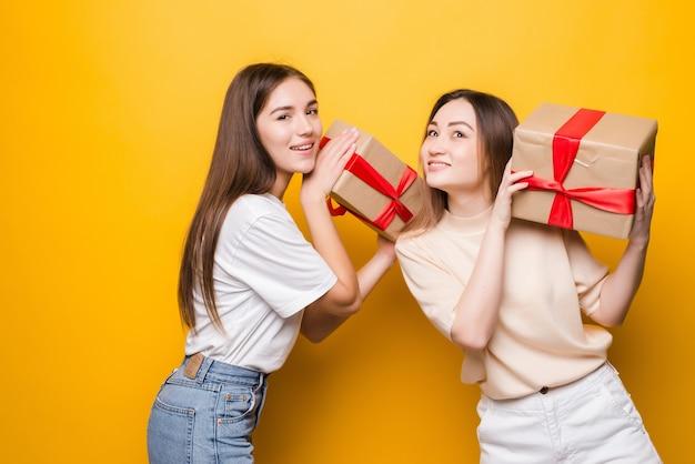 Zijaanzicht van verraste jonge vrouwen houden huidige doos met de boog van het giftlint die op gele muur wordt geïsoleerd. vrouwendag verjaardag, concept vakantie.