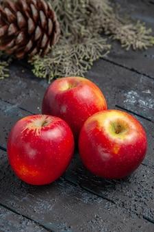 Zijaanzicht van verre appels op tafel drie geelrode appels op de grijze tafel met takken met kegel con