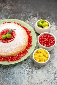 Zijaanzicht van verre cake en snoepjes granaatappelzaden citrusvruchten snoepjes een smakelijke cake