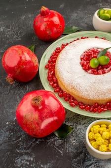Zijaanzicht van verre cakesnoepjes een smakelijke cake gele snoepjes limoenen en drie rode granaatappels