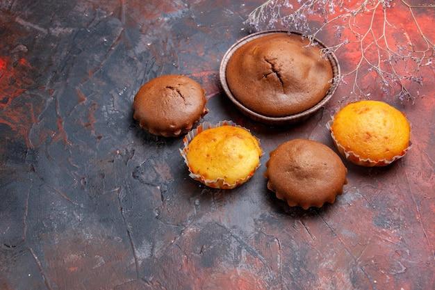 Zijaanzicht van verre cupcakes verschillende cupcakes op de blauw-rode tafel