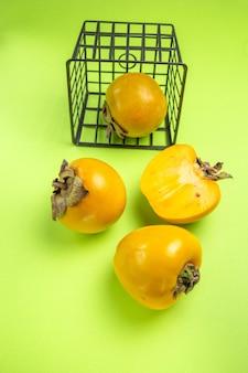 Zijaanzicht van verre dadelpruimen drie smakelijke dadelpruimen naast de mand met persimmon