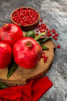 Zijaanzicht van verre granaatappels de kom met granaatappelpitjes rode granaatappels met groene bladeren