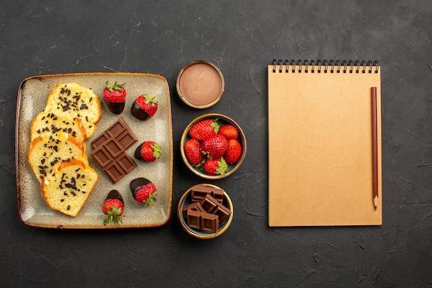Zijaanzicht van verre kopje thee met cake plaat van cake met chocolade bedekte aardbeien kopje thee chocolade crème en aardbeien in kommen naast potlood en notitieboekje