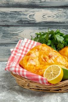 Zijaanzicht van verre taarten en citroenmand met twee taarten, kruiden, citroen en limoen en tafelkleed op de houten achtergrond