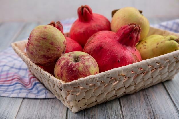 Zijaanzicht van vers fruit zoals granaatappels, appels en kweeperen op een emmer op een gecontroleerde doek op een grijze achtergrond