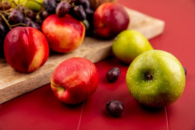 Zijaanzicht van vers fruit zoals perzikgrapanas op een houten keukenbord op een rode achtergrond