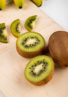 Zijaanzicht van vers kiwifruit en plakken van kiwi op een houten scherpe raad op wit