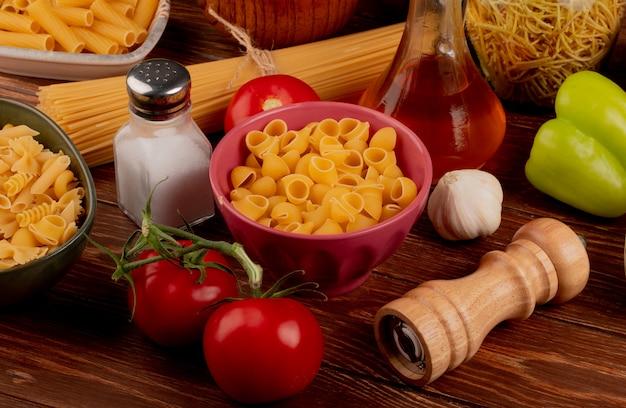 Zijaanzicht van verschillende macaronis en tomaten knoflook peper zout en gesmolten boter op houten tafel