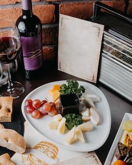 Zijaanzicht van verschillende soorten kaas met druivenmost op een witte plaat