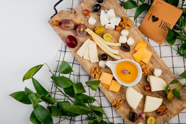 Zijaanzicht van verschillende soorten kaas met stukjes boter druiven druiven olijven noten op snijplank en ik hou van je kaart op witte tafel versierd met bladeren
