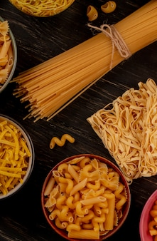 Zijaanzicht van verschillende soorten macaroni als tagliatelle van spaghettivermicelli en anderen op houten lijst
