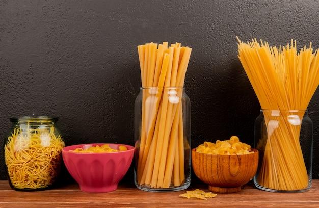 Zijaanzicht van verschillende soorten macaroni in potten en kommen op houten oppervlak en zwarte ondergrond